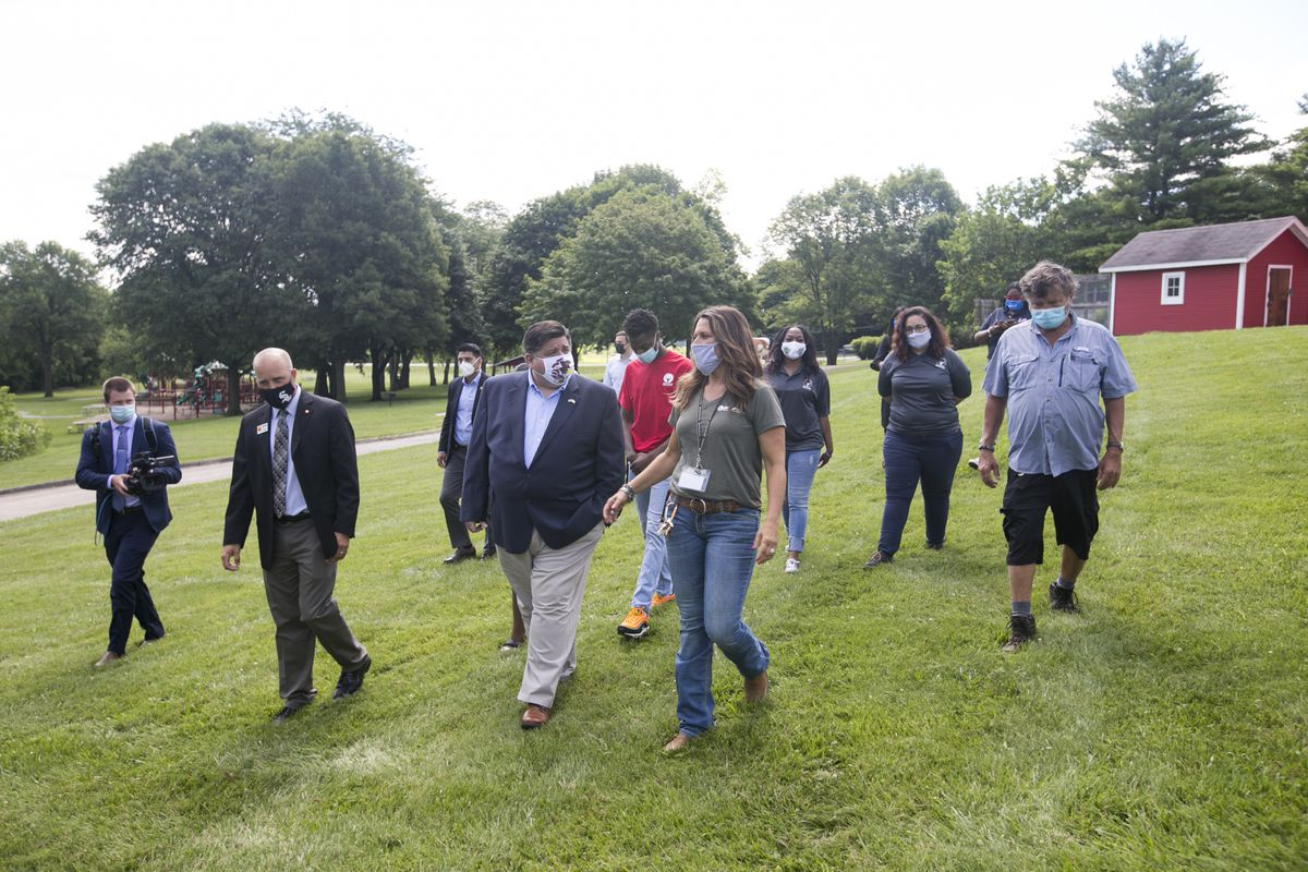 Gov. J.B. Pritzker, center, tours Lockwood Park in Rockford with Jennifer Winberg, right front, park manager, and Jay Sandine, second from left, executive director of Rockford Park District, last week.