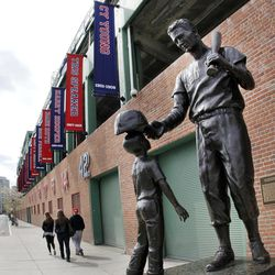 Pedestrians walk past a statue of former Boston Red Sox player Ted Williams outside Fenway Park in Boston Monday, April 9, 2012. The Boston Red Sox baseball home opener is Friday.