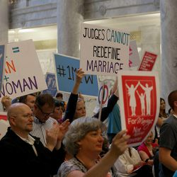 """People hold signs showing their support of marriage between one man and one woman at a """"Stand for Marriage"""" rally at the state Capitol in Salt Lake City on Tuesday, April 28, 2015."""