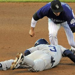 San Diego Padres' Andy Parrino (3) beats the tag at second by Colorado Rockies shortstop Troy Tulowitzki (2) on a double during the second inning of a baseball game, Monday, April 16, 2012, in Denver.