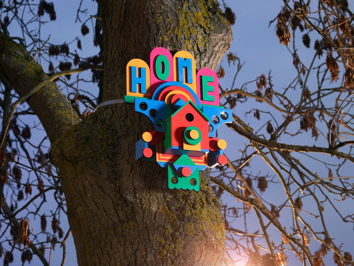 A colorful birdhouse attached to a tree. There are letters above the entrance which read: Home.