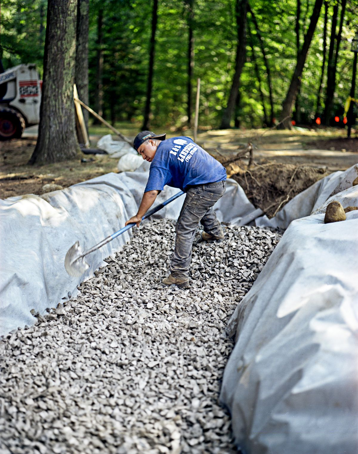 Man Digs Trench For Fieldstone Wall