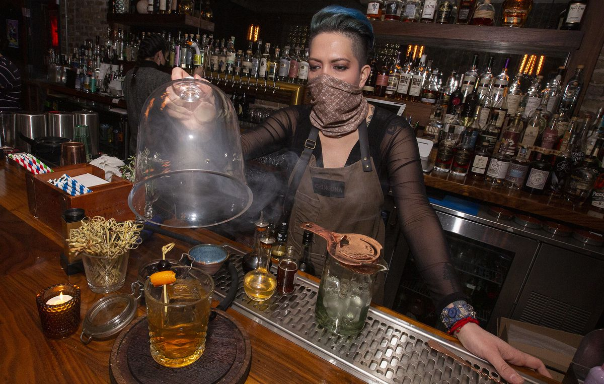 A bartender unveiling a smoked cocktail on a bar.