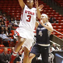 Utah's Iwalani Rodrigues flies in for a layup ahead of Utah State's Devyn Christensen as Utah and Utah State play Nov. 27, 2012, in the Huntsman Center. Utah won 92-64.