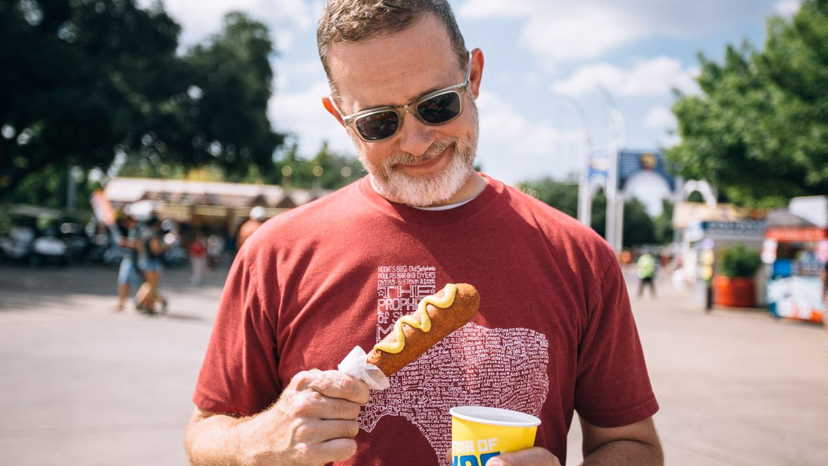 a person stares pensively at a corn dog