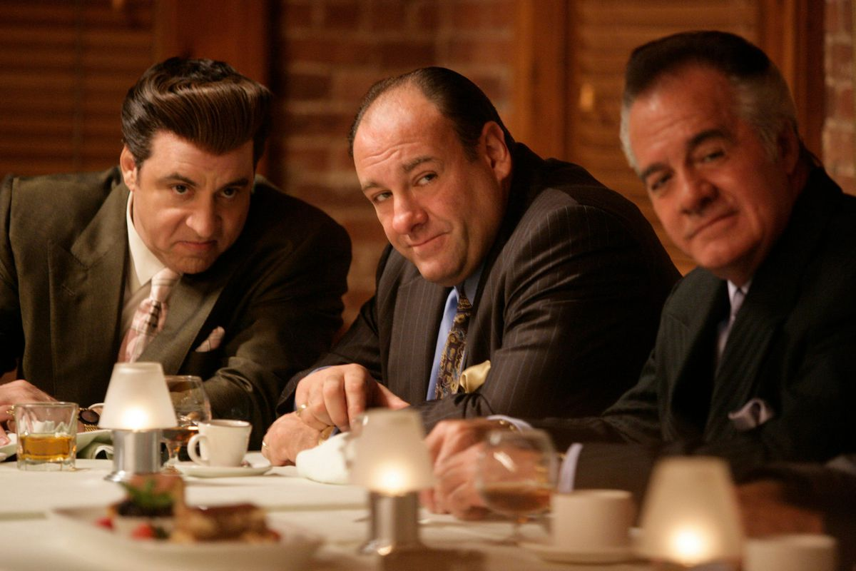 A scene from the Sopranos with James Gandolfini as Tony Soprano sitting at a table flanked by two men.