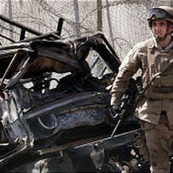 A U.S. soldier patrols after a car bombing this summer near the entrance to the Green Zone, the heart of Baghdad's U.S. zone.