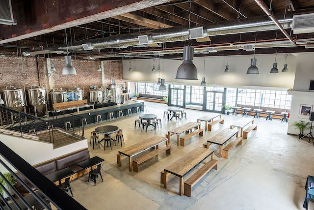 A wide shot of an open beer brewery area with communal seating.