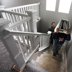 Jesus Lopez, front, and Louis Gomez install carpet at a new home in Farmington on Thursday, Feb. 4, 2016.
