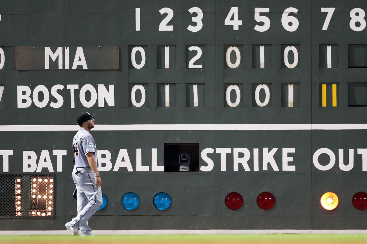 The scoreboard behind Miami Marlins left fielder Austin Dean tells the story of the 11-run Red Sox seventh inning. The Boston Red Sox host the Miami Marlins in a regular season MLB baseball game at Fenway Park in Boston on Aug. 29, 2018.
