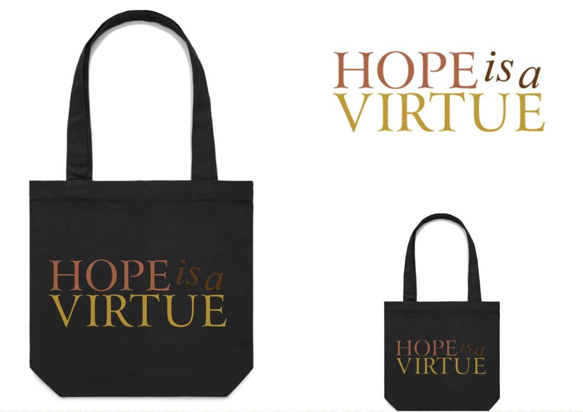 """A black tote bag that reads """"hope is a virtue."""""""