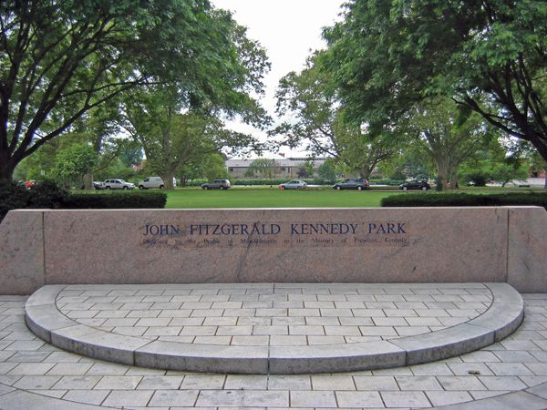 A memorial wall with writing and in front of it a half-circle of raised brick.