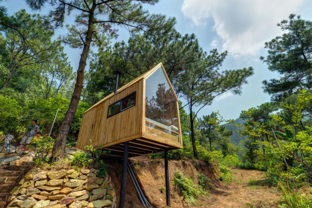Bare bones tiny house with glass wall perches on stilts curbed