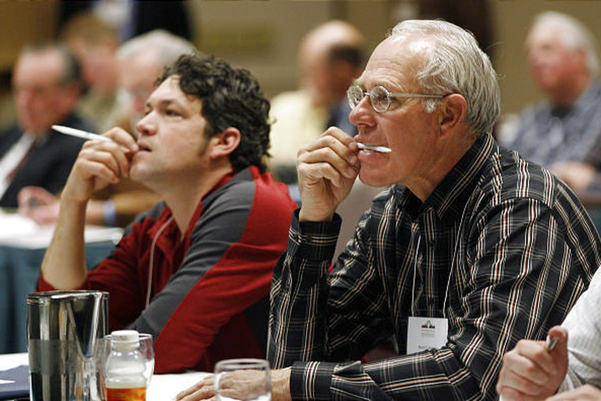 Chris Conrad, left, and Brent F. Hunter listen to speakers during a panel discussion at a sustainable farming conference.