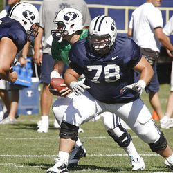 BYU offensive lineman Houston Reynolds blocks for quarterback Jake Heaps during drills at fall football camp.