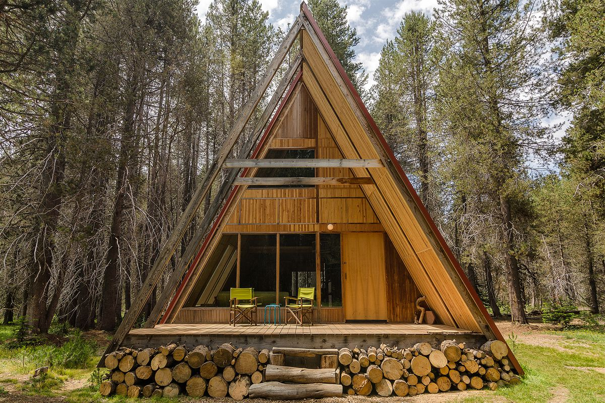 The exterior of an A-frame in California. The facade is wood and there are stacks of logs in the base.