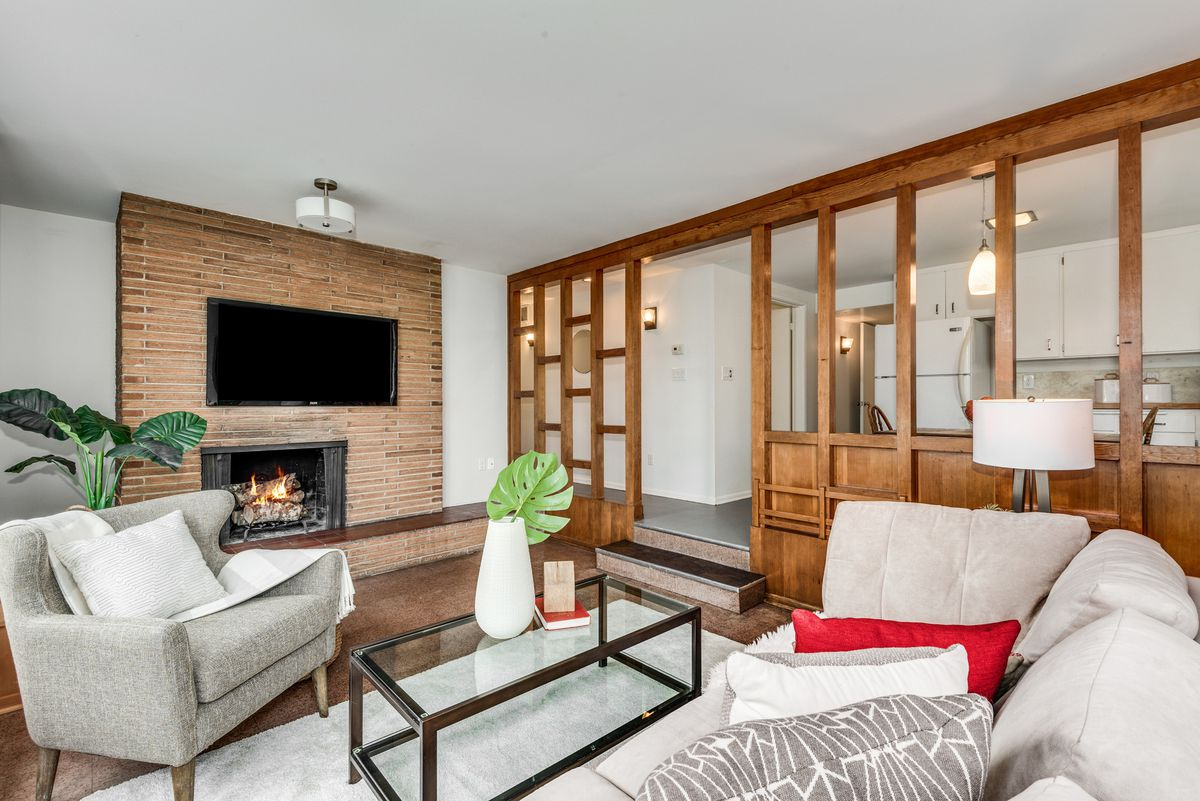 A living room with a brick fireplace, wall paneling, and couches.