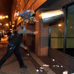 A man throws a trash can at the window of a building during a protest after George Zimmerman was found not guilty in the 2012 shooting death of teenager Trayvon Martin, early Sunday, July 14, 2013, in Oakland, Calif. Protesters angered by the acquittal Zimmerman held largely peaceful demonstrations in three California cities, but broke windows and started small street fires Oakland, police said. (AP Photo/Bay Area News Group, Anda Chu)