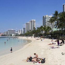 FILE - In this Monday, March 13, 2017, file photo, people relax on the beach in Waikiki in Honolulu. Many Americans might dream of going on vacation to places such as Waikiki, but a new poll shows nearly half of Americans won't be taking a summer vacation this year, mostly because they can't afford it and some because they can't get away from work.