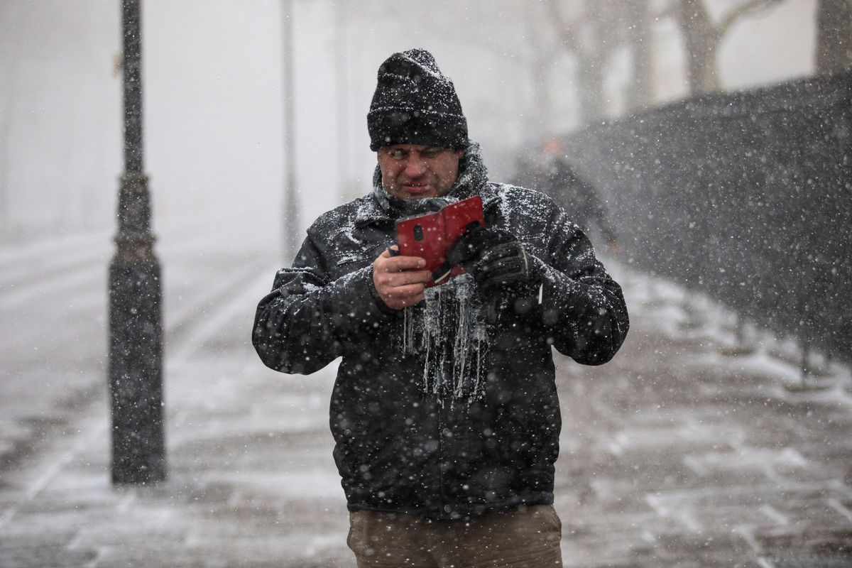 A man in a snowstorm takes a picture with his mobile phone.