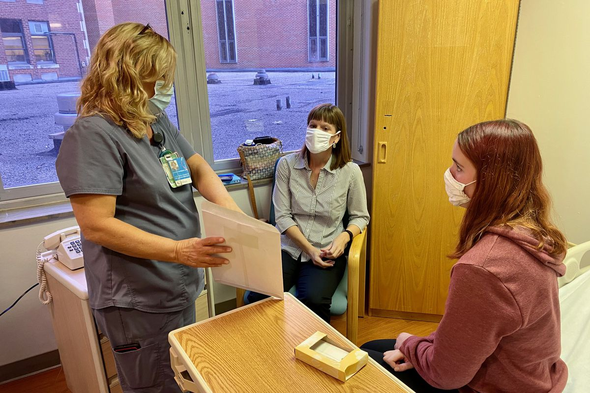A health care worker shows a piece of paper to an adolescent patient and the patient's mother in a doctor's exam room.