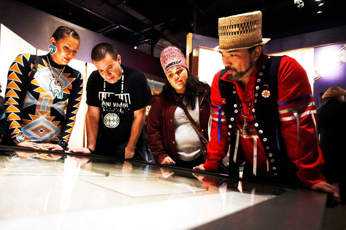 Four members of the Nisqually tribe stand and look at a document on display in a museum.