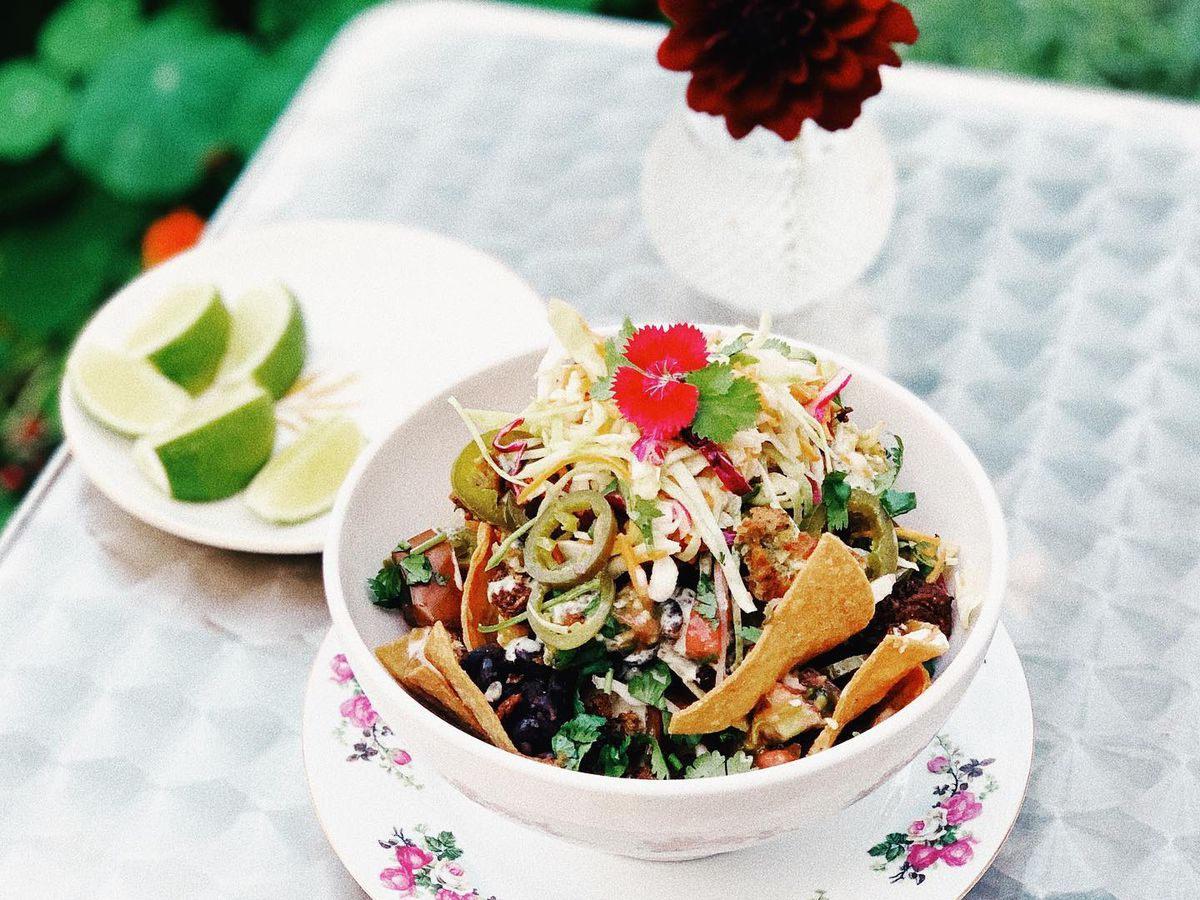 A floral decorative bowl and charger on a checkered cloth-lined table. The bowl is full of nachos, topped with a flower, beside a plate of lime wedges and a flower in a pot