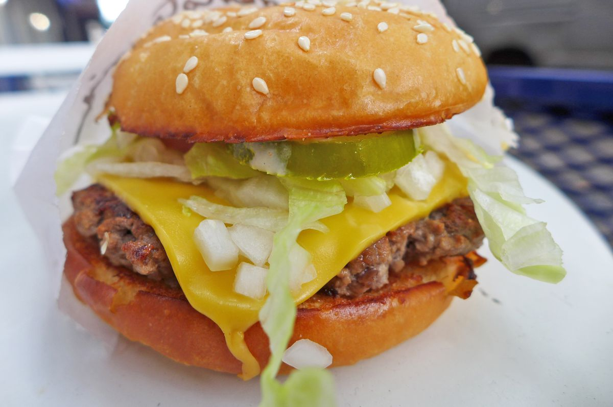 A cheeseburger with seeds on the bun and chopped onions spilling out.