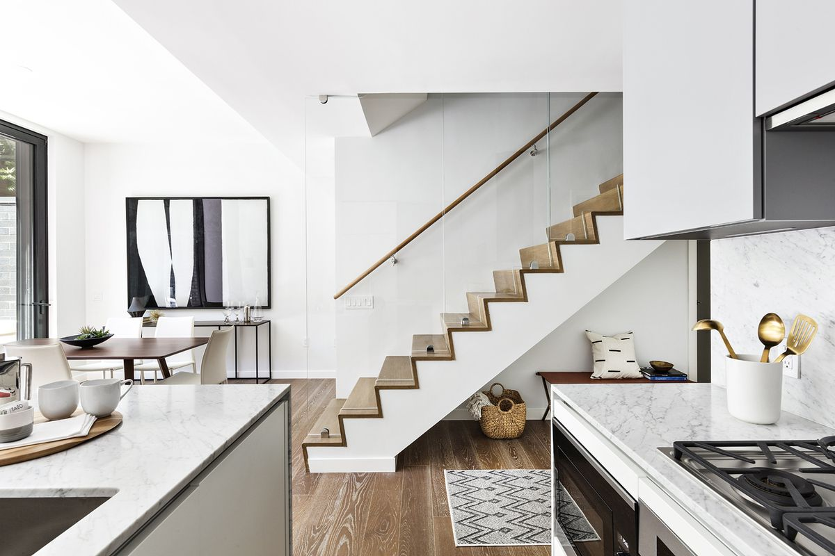 A kitchen with white cabinetry and marble counters.