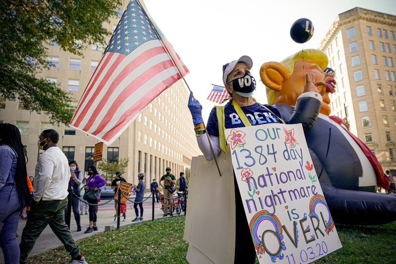"""A protester in a vote mask and Biden t-shirt holds a US flag and wears a sandwich board that reads """"Our 1384 day national nightmare is over."""" The board is decorated with flowers and rainbows."""