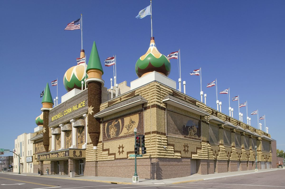 The exterior of the Corn Palace in South Dakota. The building has multiple turrets and flags on the roof. There is a sign on the front of the building that reads: Mitchell Corn Palace.