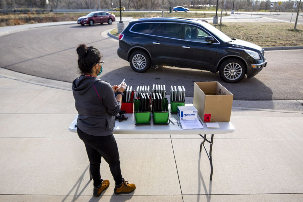 Staff distribute laptops to families at Denver's Joe Shoemaker School on March 25, 2020, as schools prepare for remote learning.