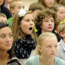 Addie Goettig, 11, reacts to seeing her father, Air Force Tech Sgt. Edward Goettig, walk down the stage at Fox Hollow Elementary School in Lehi on Thursday, March 6, 2014. Goettig had been deployed to Afghanistan since Aug. 27, 2013.