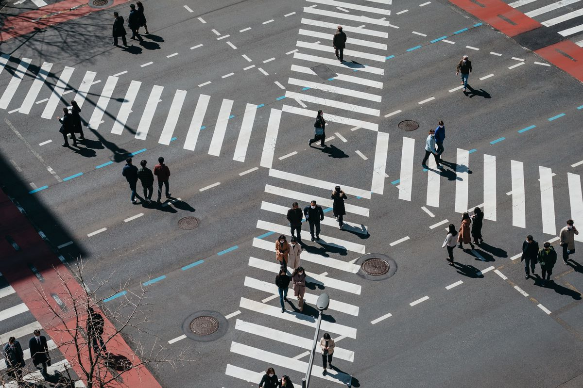 An overhead photo of people crossing an intersection on diagonal crosswalks.