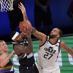 Denver Nuggets' Mason Plumlee, left, looks on as Torrey Craig, center, comes down with a rebound in front o Utah Jazz's Rudy Gobert (27) during the first half an NBA first round playoff basketball game, Tuesday, Sept. 1, 2020, in Lake Buena Vista, Fla.