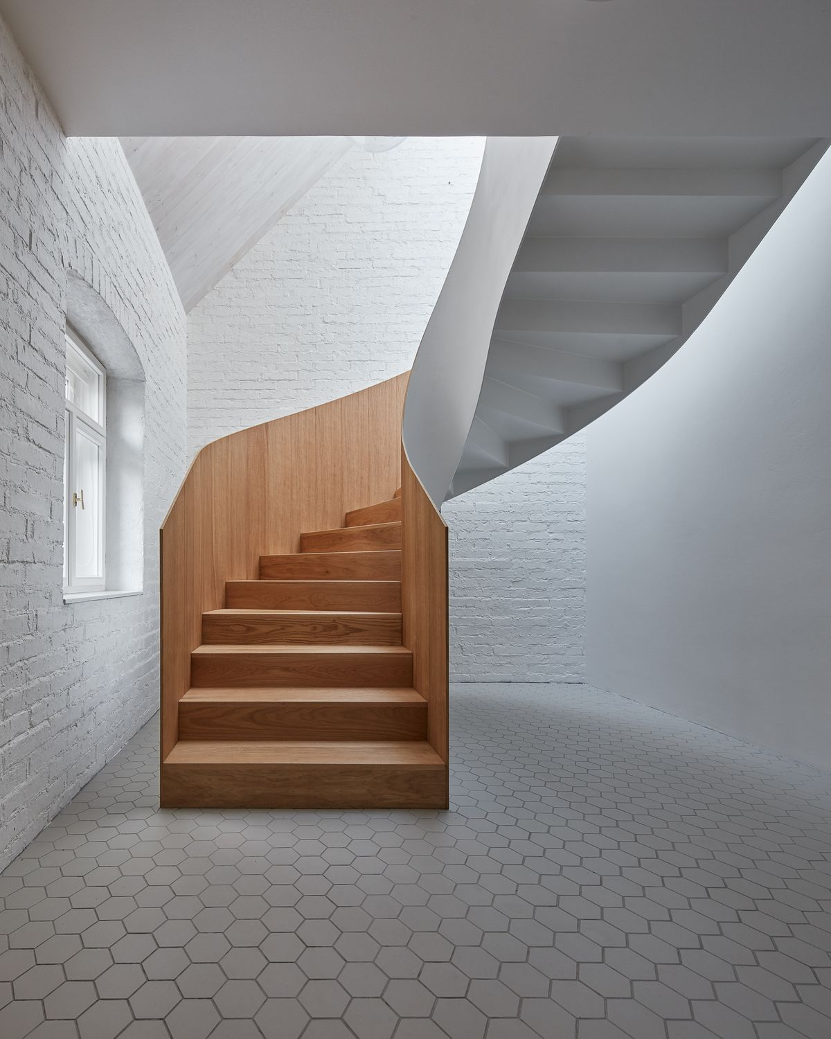Spiral staircase made from pale timber in an all-white room.