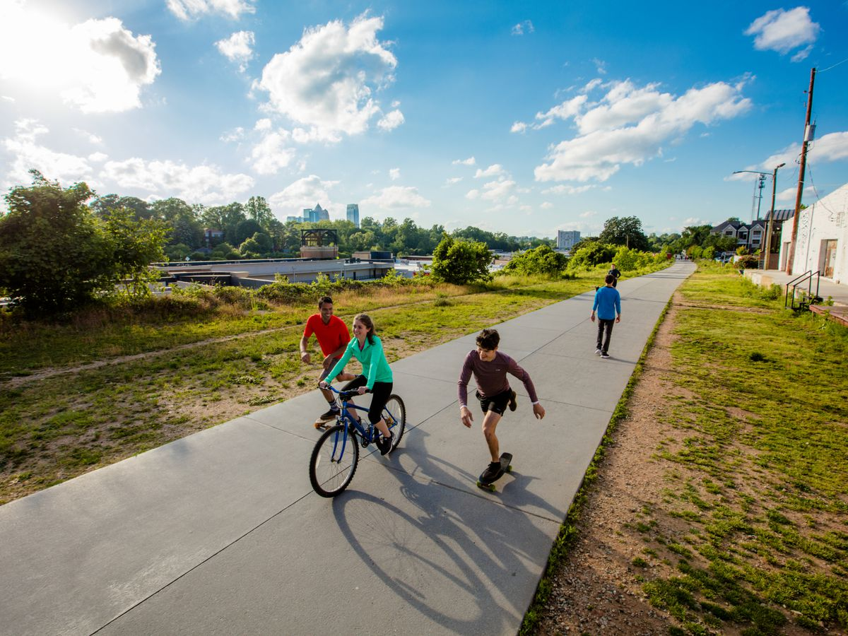 A path with grass on both sides of it. There are people riding bicycles, walking, and skateboarding on the path. In the distance is a city skyline.