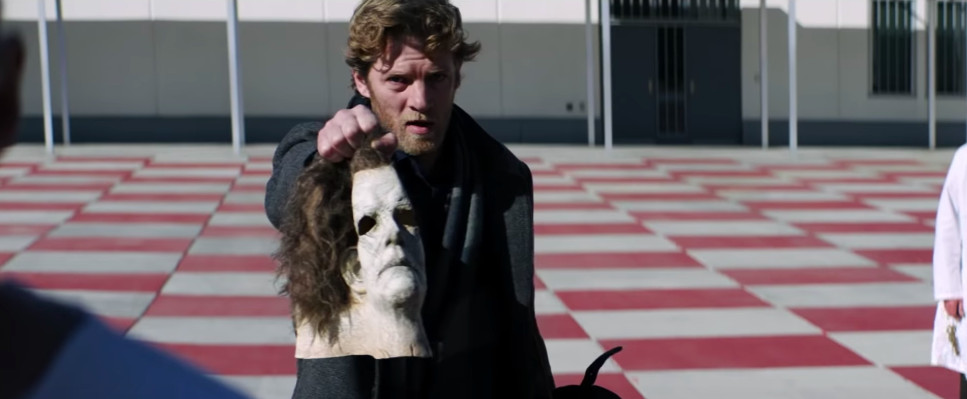 Jefferson Hall as Aaron Korey in 'Halloween,' holding up Michael Myers's old William Shatner mask