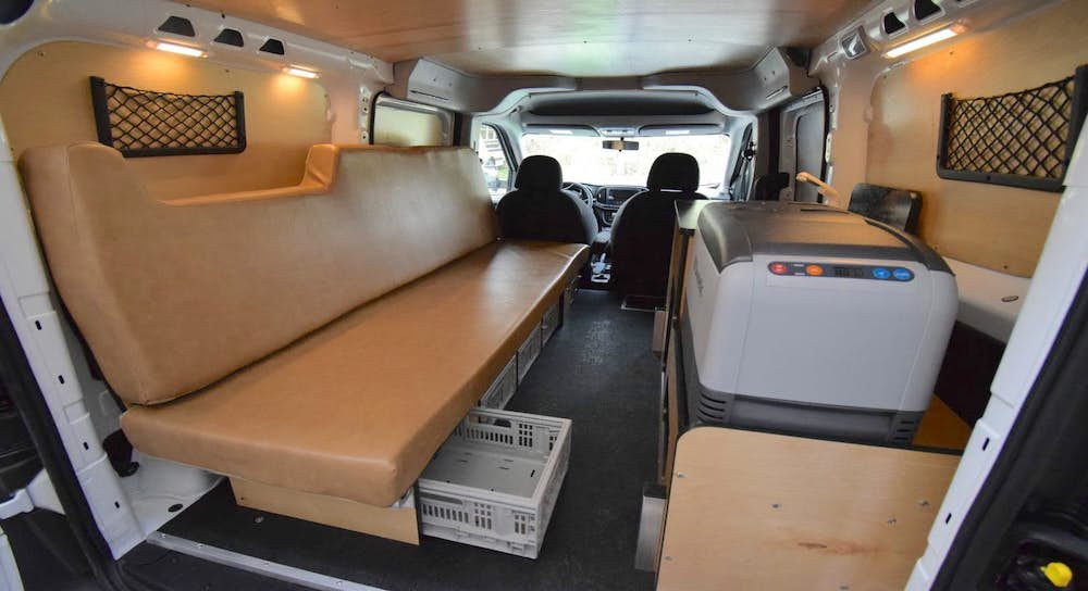 The interior of a camper van. There is a seat and various other storage compartments.