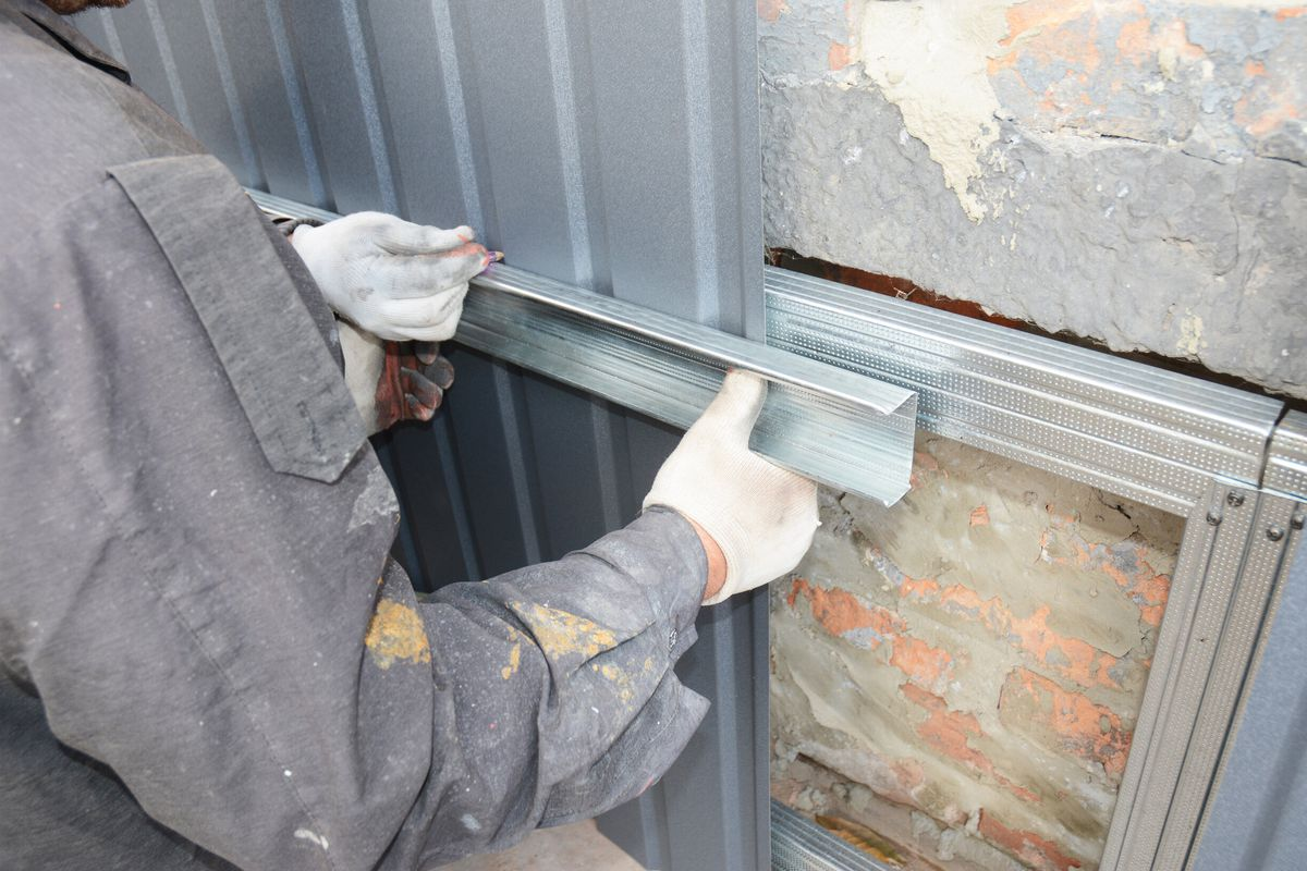 Foundation repair specialist wearing white gloves repairs brick exterior foundation of a home.