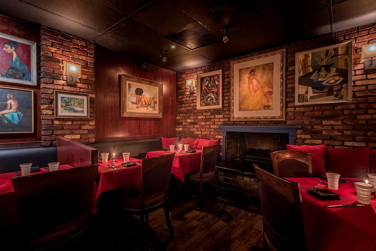 Inside Dear John's, with red booths and dim lighting and lots of art on brick walls.