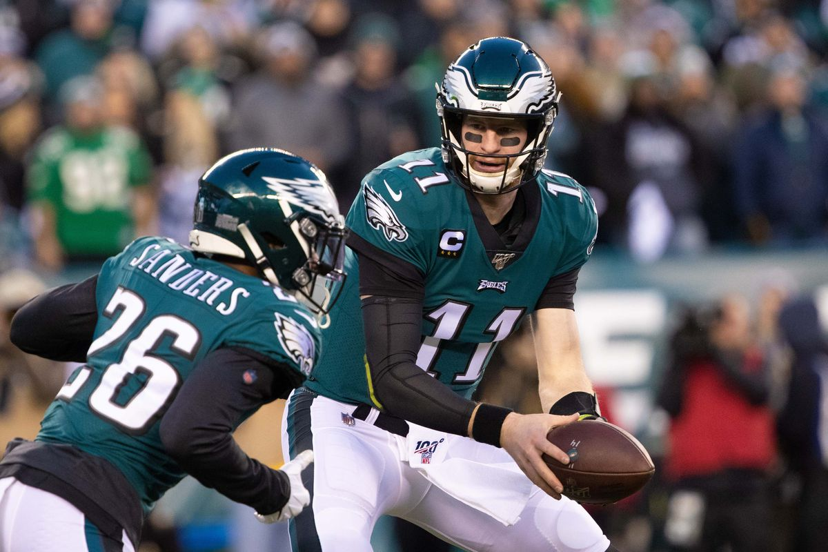 Philadelphia Eagles quarterback Carson Wentz hands off to running back Miles Sanders (26) against the Seattle Seahawks during the first quarter in a NFC Wild Card playoff football game at Lincoln Financial Field.