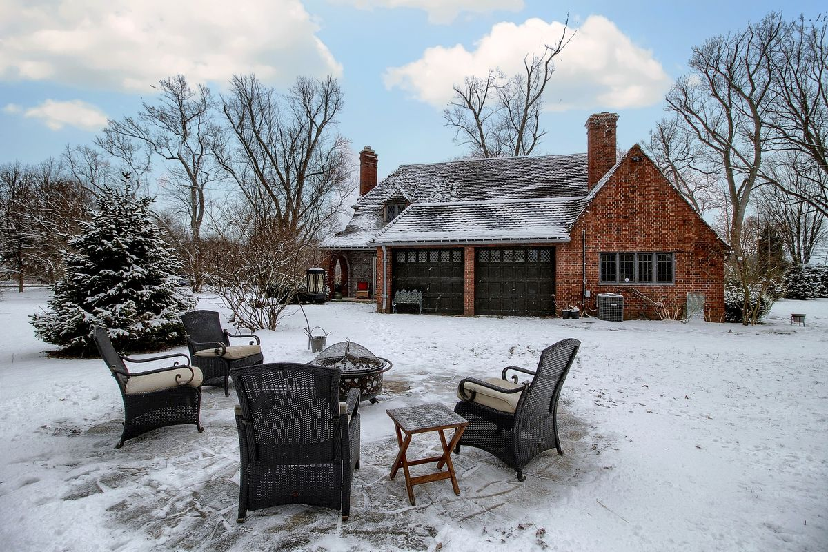 View of the back yard. Wicker chairs surround a fire pit. Snow covers everything.