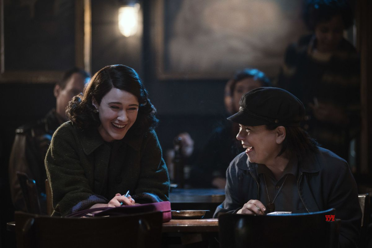Mrs. Maisel and her friend laugh at a table