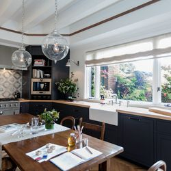 """The family kitchen was designed by Alison Davin of <a href=""""http://jutehome.com/"""">Jute</a>. The European-style kitchen has warm woods and leather pulls, herringbone flooring, and a fireplace seating area.  [Photo by <a href=""""http://www.patriciachangphotog"""