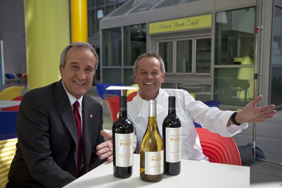 Two men sit at a table with three bottles of wine in front of them.