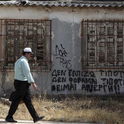 A pedestrian passes an empty house with graffiti on the wall reading  ''I hope for nothing, I fear nothing, I am jobless''  in Athens, Thursday, Sept. 6, 2012.  Greece's unemployment rate surged to 24.4 percent in June, according to official figures Thursday, as protests continued against a massive new austerity package, with police blocking their colleagues from starting work.