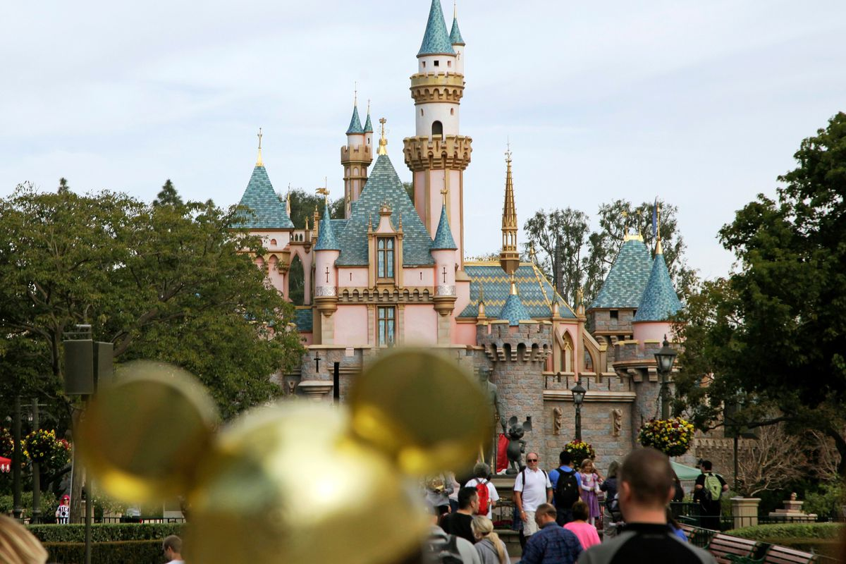 FILE - In this Jan. 22, 2015 file photo, visitors walk toward Sleeping Beauty's Castle at Disneyland Resort in Anaheim, Calif. Authorities say thieves made off with 8,000 Disneyland tickets when they stole a box trailer from a youth agricultural education