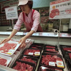 """A South Korean store employee sets out packs of domestic beef on the shelves at a Lotte Mart store in Seoul, South Korea, Wednesday, April 25, 2012. Two major South Korean retailers, including Lotte Mart,  suspended sales of U.S. beef Wednesday following the discovery of mad cow disease in a U.S. dairy cow. Reaction elsewhere in Asia was muted with Japan saying there's no reason to restrict imports. The letters on a card at left top read """" Starting from the 25th, we will temporarily stop the sales of the US beef. Thank you for your understanding""""."""