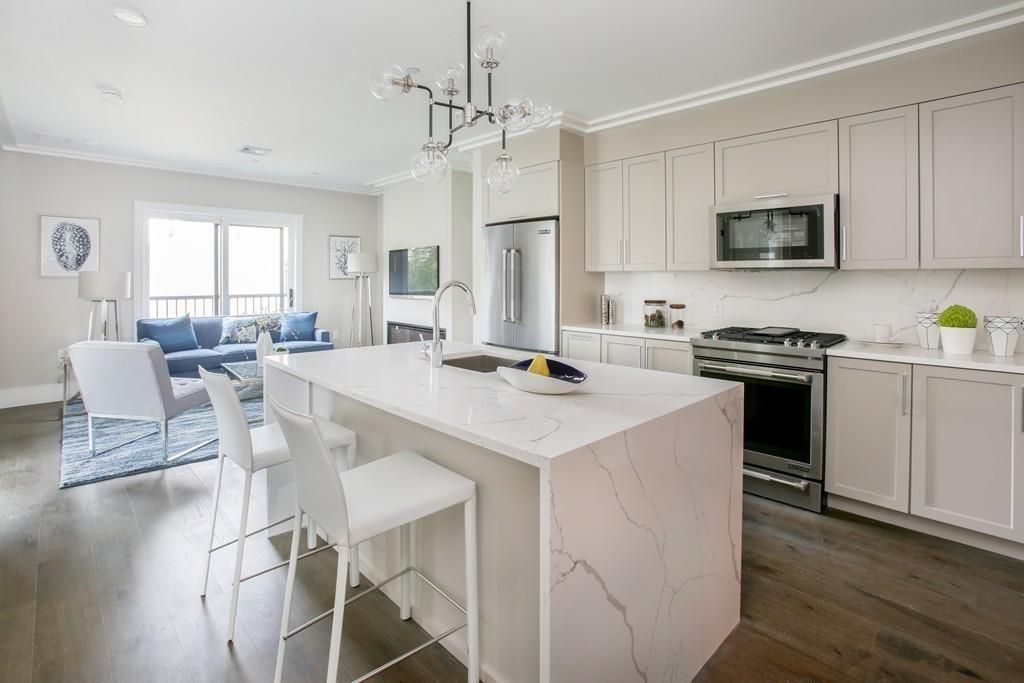 A spacious, open modern kitchen next to a living room, and the kitchen has a large island.